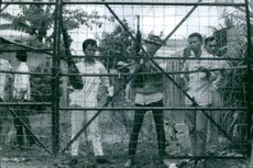 A vintage photo of Vietnamese men holding guns while in their post guarding the base.