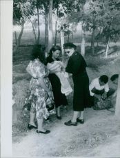 A vintage photo of a policewoman checks the baby being cuddled by a woman while a policeman is checking the bag that they carried. A protocol during a war in Russia.