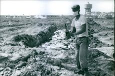 A man standing on the mass grave land and holding a bottle with surgical mask in Vietnam, 1968.