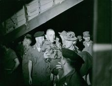 A vintage photo of a soldier being carried by his comrades after fatalities brought by war in Vietnam.