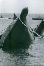 A navy standing on a ship that were flip during a war in France and were trying to tie a rope for the ship to be pulled and turn upside , 1970.