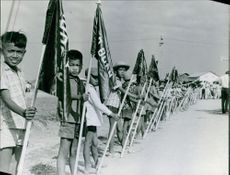 A vintage photo of children standing in a row holding flags of the country during a visit of Vice President Hubert H. Humphrey in Saigon, February 1966.