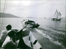 A soldier is aiming his gun at the other sailboat, targeting the enemy down that crossed the shores of the enemy line.