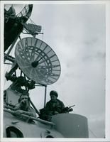 A vintage photo of a man in a radio making a feedback to the headquarters while the other soldier is looking at him holding a rifle; both were guarding the satellite disk.