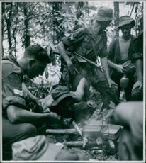 Coldstream Guards on patrol.- While some of the party build the bamboo huts, others prepare the meal. Here a fire is kindled to brew the heavy, black tea , the standard drink of the patrolling Guardsmen.