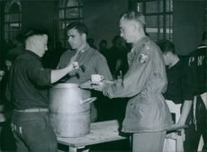 The kitchen staff at the university are all German prisoners of war working under American supervision. Here  getting  service is 1st Lt. William L. Bridges of Kansas City, who is studying accountancy at the university.