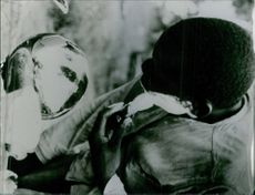 A man is putting a cream on his face while looking at his reflection taken in Kongo Africa, 1965.