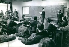 A professor is giving a lectures and strategy to air pilots during German war.