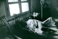 A vintage photo of a patients lying in a hospital bed, they are victims during Vietnam war.