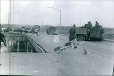 A vintage photo of a military service on their way to Vietnam passing the flyover that is on its pavement work.