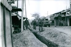 A vintage photo of Viet soldiers walking near a man-made canal road walking to the main city during a war in Vietnam.