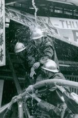 A vintage photo of firemen helping hand in hand in holding the fire hose to control the fire that struck one of Saigon area.