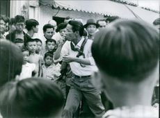A Vietnamese preacher with a snake around his neck being watched in public.