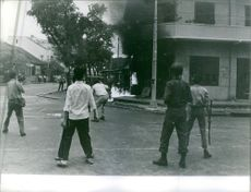 A vintage photo of a fire in one of Saigon street while men, soldiers and photographer were looking at during Vietnam war.
