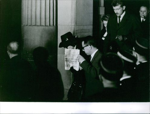 A photo of Maurice trying to get out from a building, with a cover of news paper he trying to hide himself from the press. 1961.
