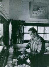 A photo of  a Canadian-American actor Raymond Burr preparing a food.
