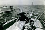 Year ?  A photo of a French Socialist politician Gaston Defferre in a boat, looking towards the camera and smiling.