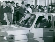 A photo of a French Socialist politician Gaston Defferre in a vehicle, waving and smiling, photographers, gathered around taking pictures in a crowd of people. 1964