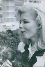 A side view photo of Jill Haworth while she's holding a dog.