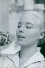 A photo of Jill Haworth. Someone is trying to put a lipstick on her lips. 1960