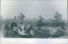 A photo of Soviet troops advance against German positions in East Prussia, under covering fire from machine-guns, 1944.