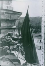 A Soldier placing the flag on the roof. 1944