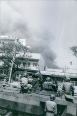 Soldiers on the tank watching a building burning on fire, in Saigon, 1968.