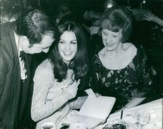 Dorothy MacGowan, with two other people, writing something on a notebook.
