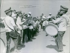 Children playing musical instruments for a welcome parade.