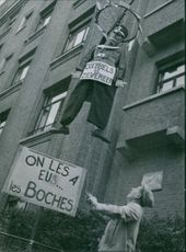 """Man is pulling the string that hangs a soldier like as a symbol for Nassi soldiers surrender during war, while a logo word says """"we had them the Krauts"""" in Brussels, 1945."""