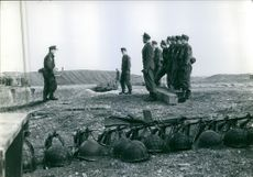 Soldiers stand side by side and looks at the person in front of them while their hats and rifle are placed on the ground during war in Germany, 1960.