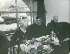 Jean-Claude Killy with a group of people eating and laughing together.