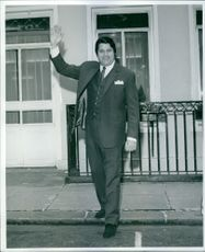 Solomon King on the street, waving his right hand.