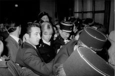 Alain Delon surrounded by people.