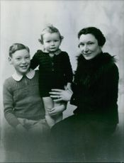 Woman with her children posing and smiling.