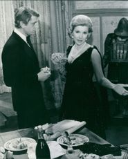 Susan Hampshire standing and talking to a man standing next to her.