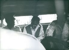 Nahashon Isaac Njenga Njoroge seated in between two police officers inside the prison van. 1969.