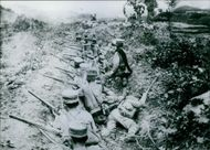 Japanese soldiers shooting their rifles from a trench.