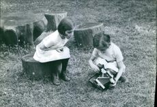 Children siting and playing in the park, holding toy.  1966
