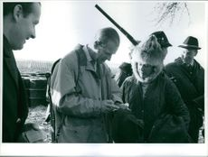A photo of Prince Philip , Duke of Edinburg examining a bottle in his hands while in a conversation.