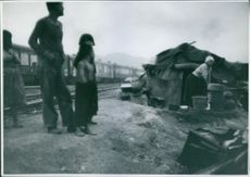 Family standing in front of their shelter beside railway track.