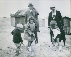 A photo Prince Philip holding a shovel (left) Helen Foufouni (Helen Cordet) (middle) and her brother Jean Foufouni with Prince Philip father and mother standing behind. 1926
