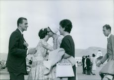 Juan Carlos I of Spain is talking with a lady, while another two ladies are hugging