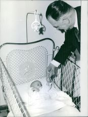 Father playing and holding hand of a newly born baby inside the carry cot in a nursery.