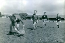 Children playing rugby on the field, 1963.
