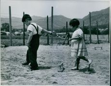 2 children, a boy and a girl, playing on the field.