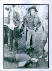 A man lying on the ground. Men are standing and watching.