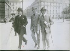 Otto Christian Archibald walking with other people in the street.