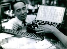Man showing jewellery piece in Japan.
