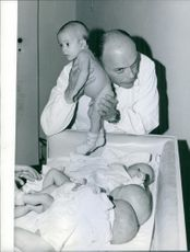 A man  holding a new born baby in a nursery room.
